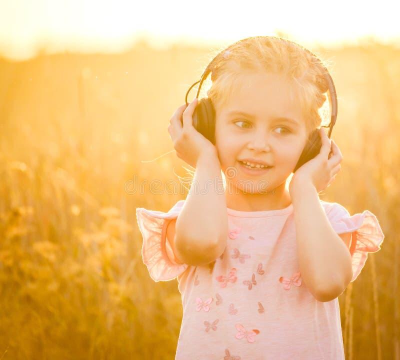 Pequeña muchacha rubia sonriente listenning a la música fotos de archivo libres de regalías