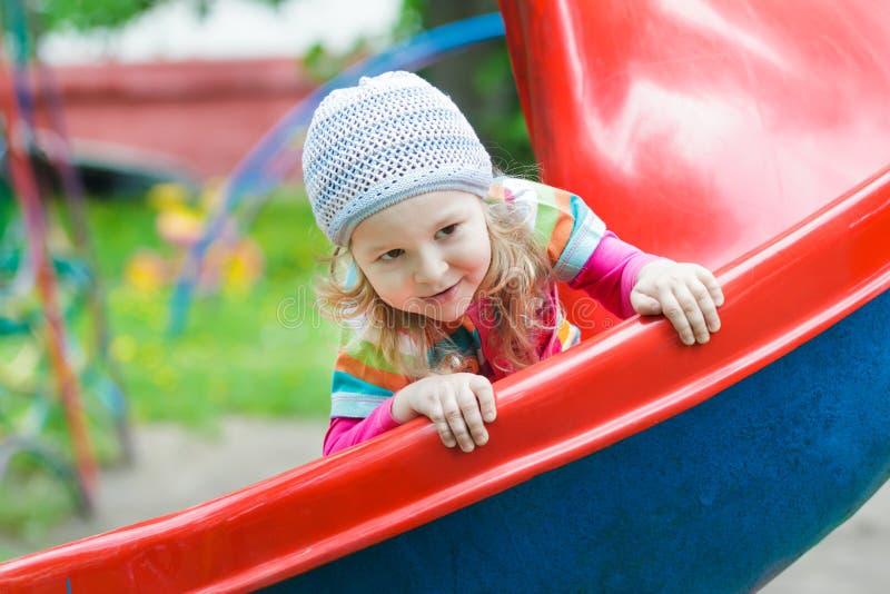 Pequeña muchacha rubia sonriente que desliza abajo la diapositiva plástica roja del patio al aire libre el la primavera imagenes de archivo