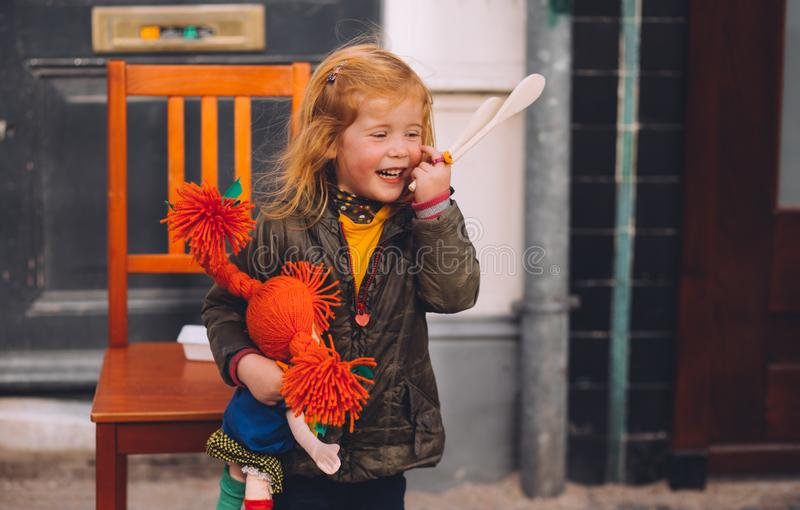 Pequeña muchacha rubia y su muñeca anaranjada en festividad del día del ` s del rey, Países Bajos del pelo imágenes de archivo libres de regalías