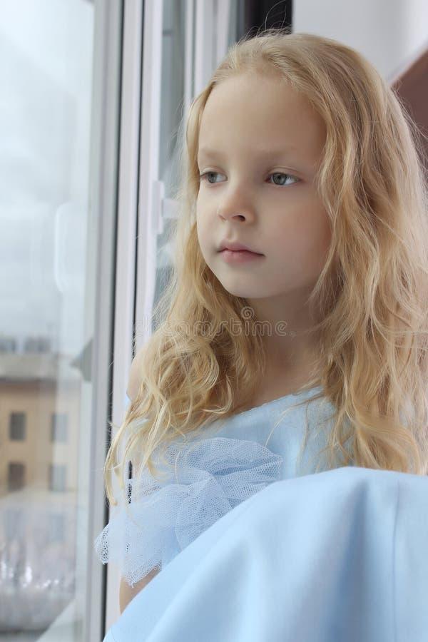 Pequeña muchacha sola que mira hacia fuera la ventana imágenes de archivo libres de regalías