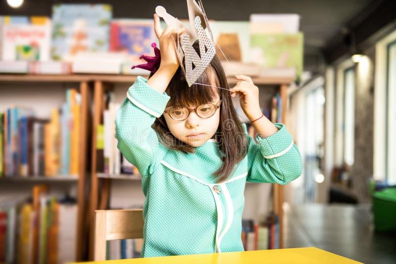 Pequeña muchacha soleada hermosa que lleva el vestido azul y la pequeña corona imagen de archivo libre de regalías