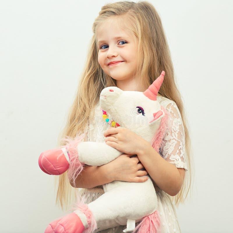 Pequeña muchacha sonriente con el juguete blanco del unicornio fotografía de archivo