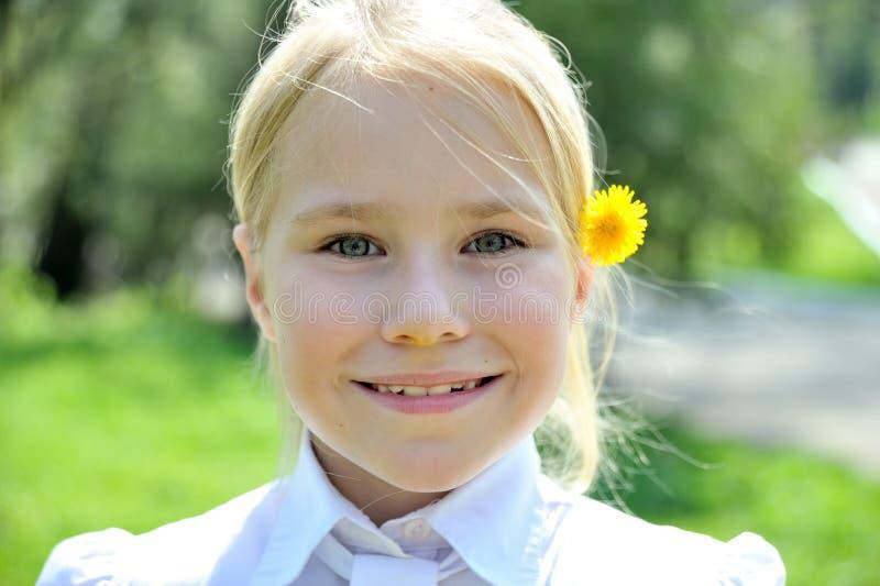 Pequeña muchacha sonriente con un retrato del diente de león imagen de archivo libre de regalías