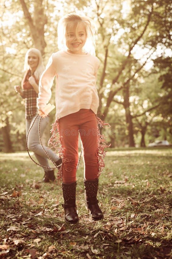 Pequeña muchacha sonriente en el parque que lleva a cabo la cuerda el jugar en parque imagen de archivo libre de regalías