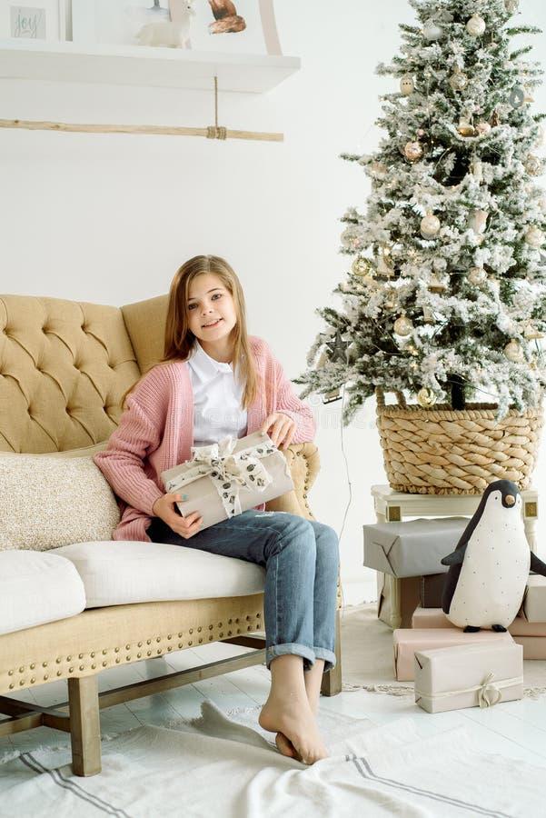 Pequeña muchacha sonriente feliz con la caja de regalo de la Navidad foto de archivo