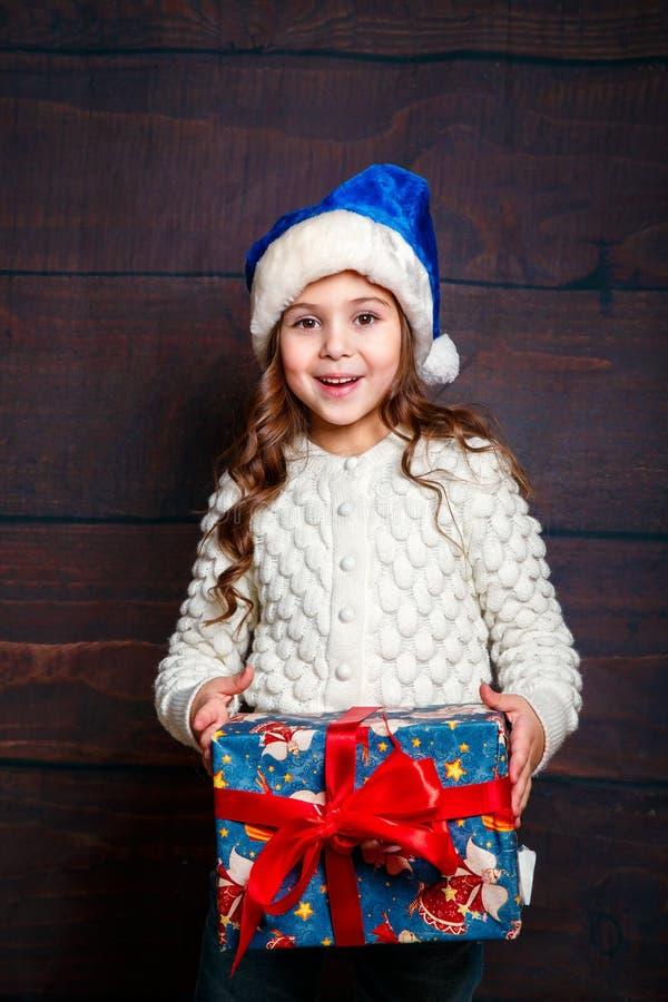 Pequeña muchacha sonriente feliz con la caja de regalo de la Navidad Concepto de la Navidad Muchacha divertida sonriente en el so foto de archivo
