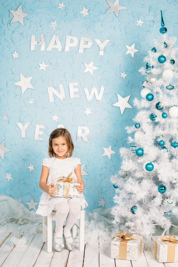 Pequeña muchacha sonriente hermosa con un regalo en sus manos imágenes de archivo libres de regalías