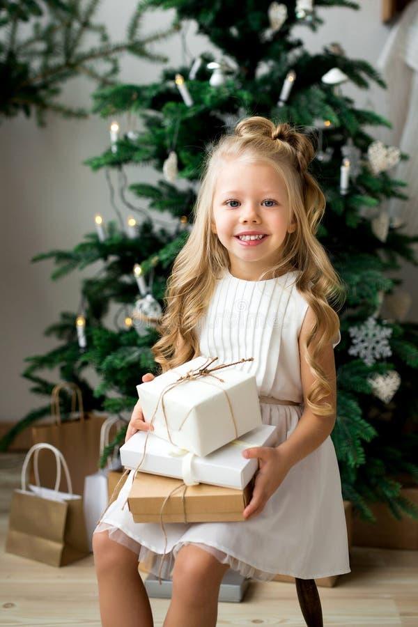 Pequeña muchacha sonriente linda feliz con la caja de regalo de la Navidad Feliz Navidad y buenas fiestas foto de archivo
