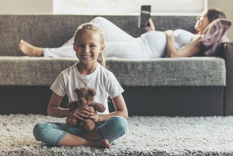 Pequeña muchacha sonriente que detiene a Teddy Bearat Home imagen de archivo libre de regalías