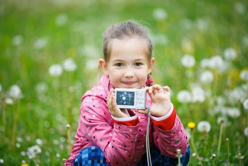 Pequeña muchacha sonriente que muestra orgulloso su fotografía foto de archivo libre de regalías