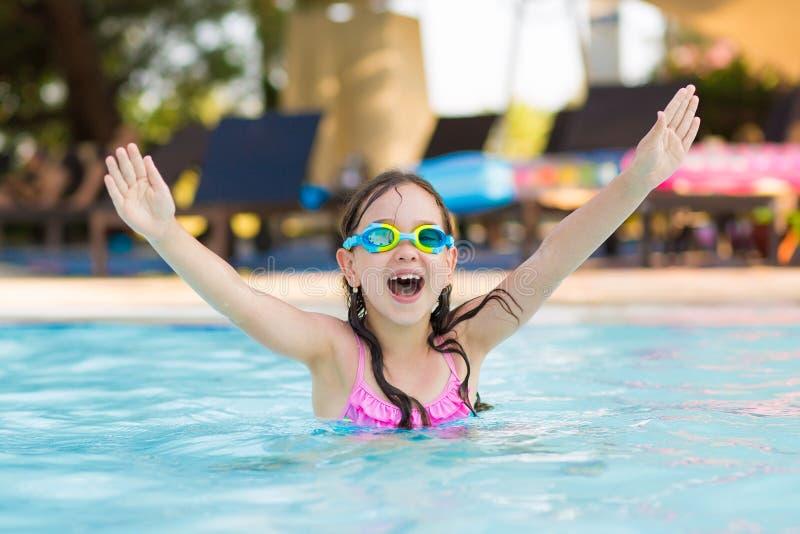 Pequeña natación feliz de la muchacha en la piscina al aire libre con los vidrios que se zambullen en un día de verano soleado imagen de archivo