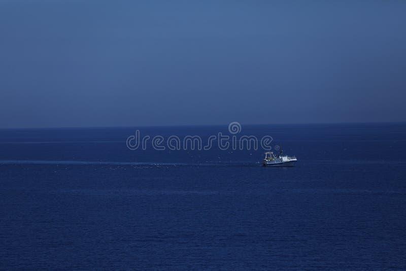 Pequeña nave que cruza en el mar fotografía de archivo