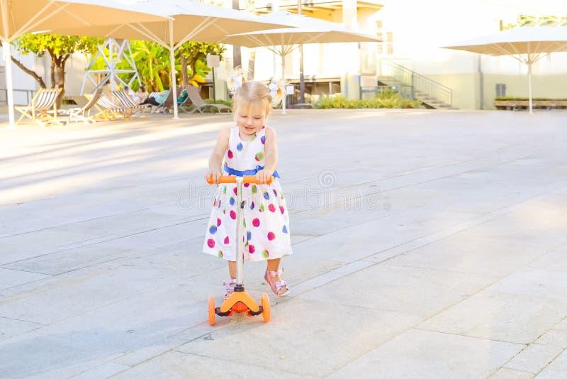Pequeña niña pequeña blondy linda en vespa del montar a caballo del vestido en la zona de recreo del parque de la ciudad con el t imagen de archivo libre de regalías