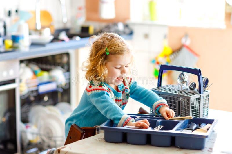 Pequeña niña pequeña linda que ayuda en la cocina con la lavadora del plato Niño rubio sano feliz que clasifica los cuchillos foto de archivo libre de regalías