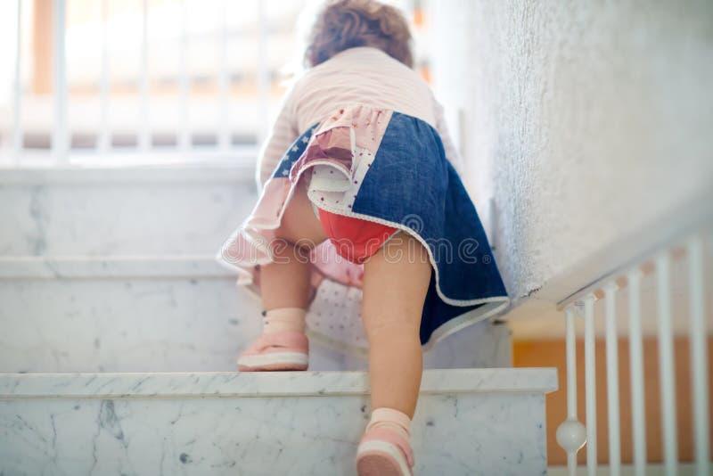 Pequeña niña pequeña linda que sube en las escaleras en casa Bebé que aprende y que hace los primeros pasos, altas escaleras imagenes de archivo