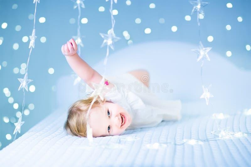 Pequeña niña pequeña en cama entre las luces azules chispeantes imágenes de archivo libres de regalías