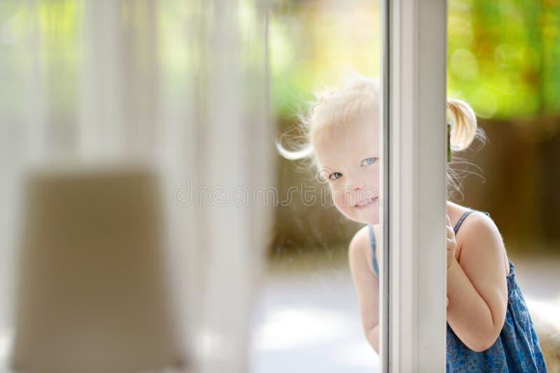 Pequeña niña pequeña linda que mira a escondidas en una ventana fotografía de archivo