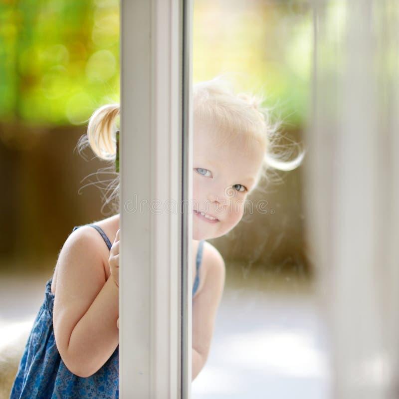 Pequeña niña pequeña linda que mira a escondidas en una ventana imagen de archivo libre de regalías
