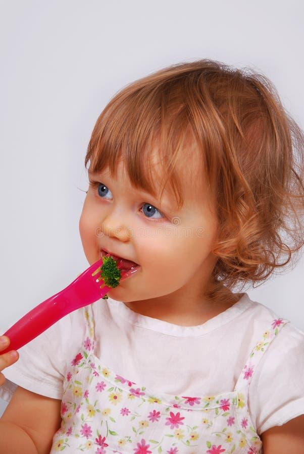 Pequeña niña que come el bróculi con la fork fotos de archivo
