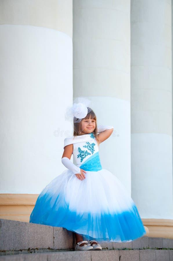 Pequeña novia. Una muchacha en una alineada de boda blanca y azul enorme fotografía de archivo
