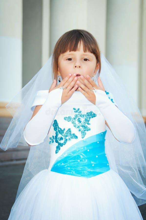 Pequeña novia Una muchacha en una alineada de boda blanca y azul enorme y imágenes de archivo libres de regalías