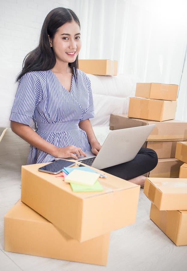 Pequeña oficina asiática joven del propietario de negocio en casa, empaquetado en línea del márketing y entrega imagen de archivo