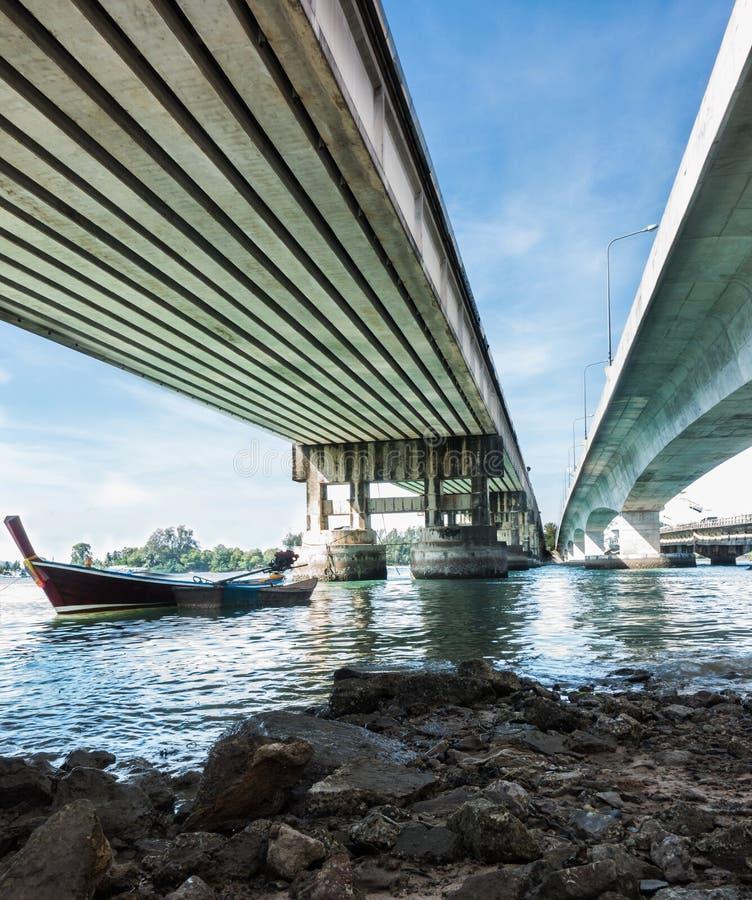 Pequeña parada de madera del barco de pesca en el río debajo de un puente imagen de archivo libre de regalías