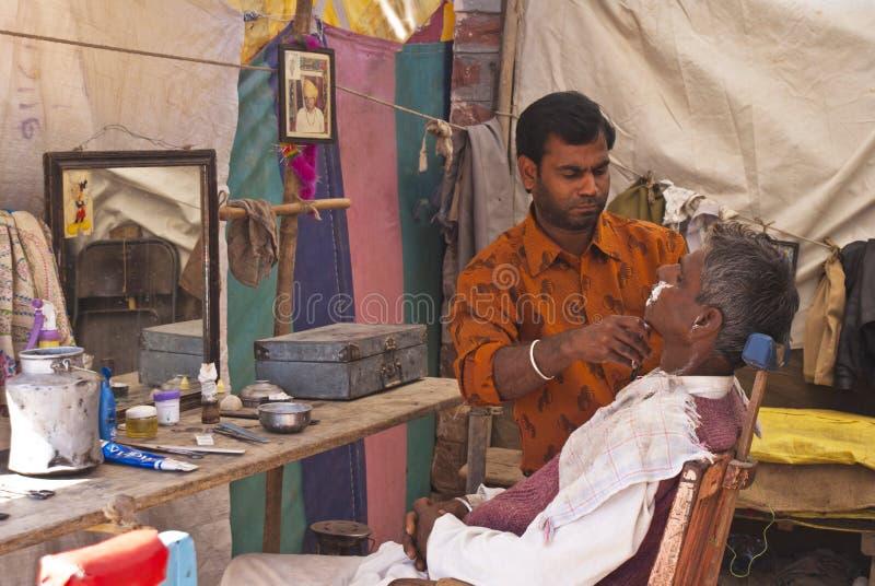 Pequeña peluquería de caballeros típica de la India en tienda a lo largo de la calle imágenes de archivo libres de regalías
