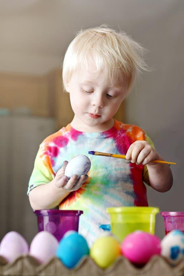 Pequeña pintura linda del niño pequeño en un huevo de Pascua foto de archivo libre de regalías