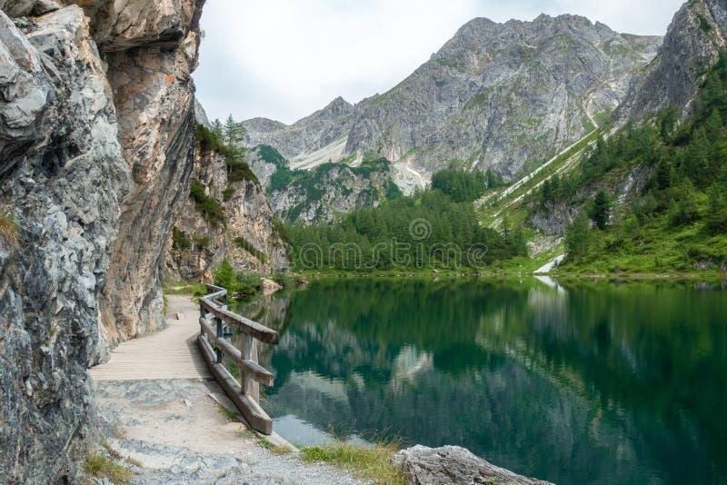 Pequeña pista de senderismo entre el lago y las montañas magníficos, Salzburg, Austria fotos de archivo