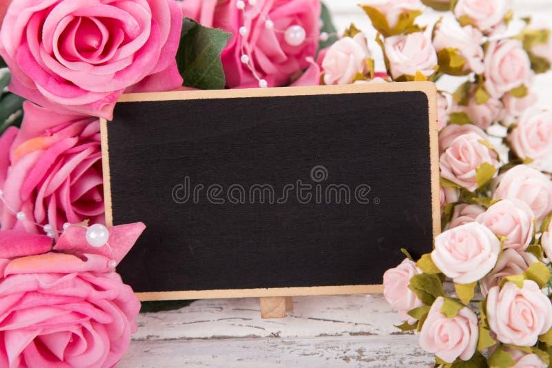 Pequeña pizarra en blanco para el día del ` s, de la madre o de la mujer de la tarjeta del día de San Valentín Fondo con las rosa imagen de archivo libre de regalías