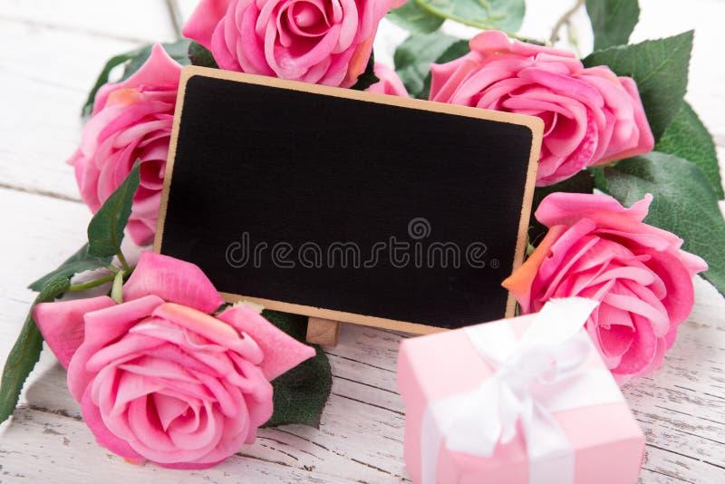Pequeña pizarra en blanco para el día del ` s, de la madre o de la mujer de la tarjeta del día de San Valentín Fondo con las rosa fotos de archivo libres de regalías