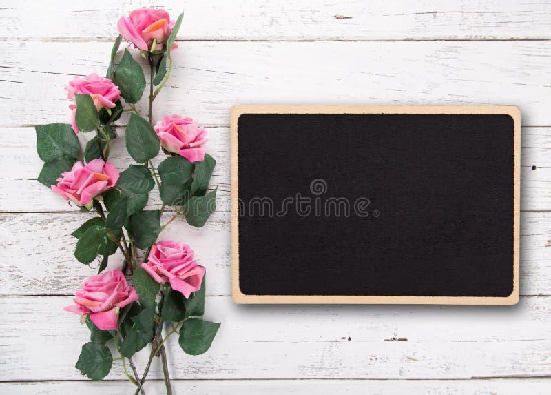 Pequeña pizarra en blanco para el día del ` s, de la madre o de la mujer de la tarjeta del día de San Valentín Fondo con las rosa fotos de archivo