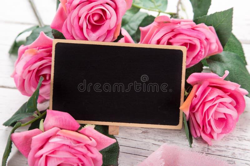Pequeña pizarra en blanco para el ` s de la tarjeta del día de San Valentín o el día de la mujer de la madre Fondo con las rosas  imagen de archivo