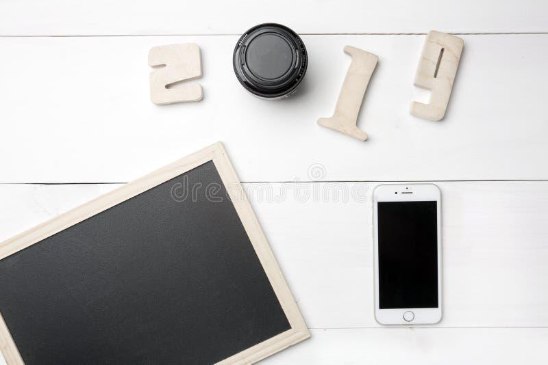Pequeña pizarra o pizarra vacía y teléfono móvil y dígitos de madera del recorte que forman número del Año Nuevo 2019 con la foto imagen de archivo