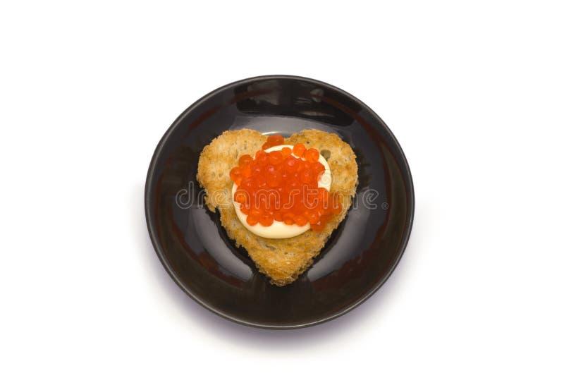 Pequeña placa con la tostada en forma de corazón con el caviar fotografía de archivo libre de regalías