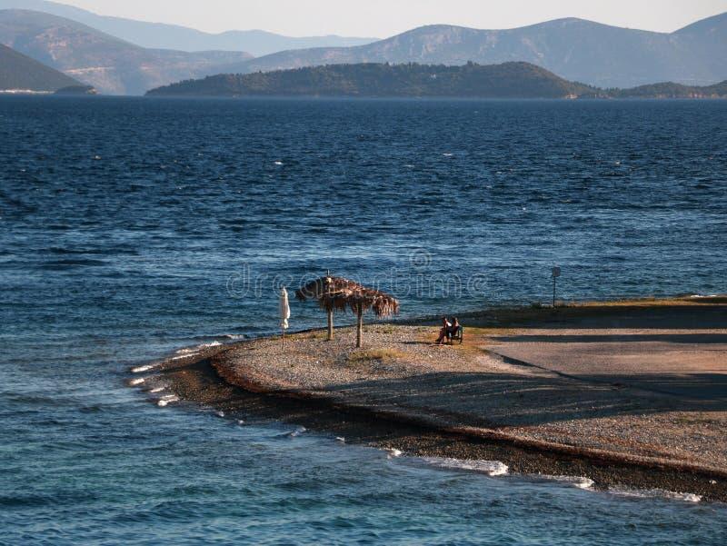Pequeña playa de la playa con un banco y los parasoles fotos de archivo