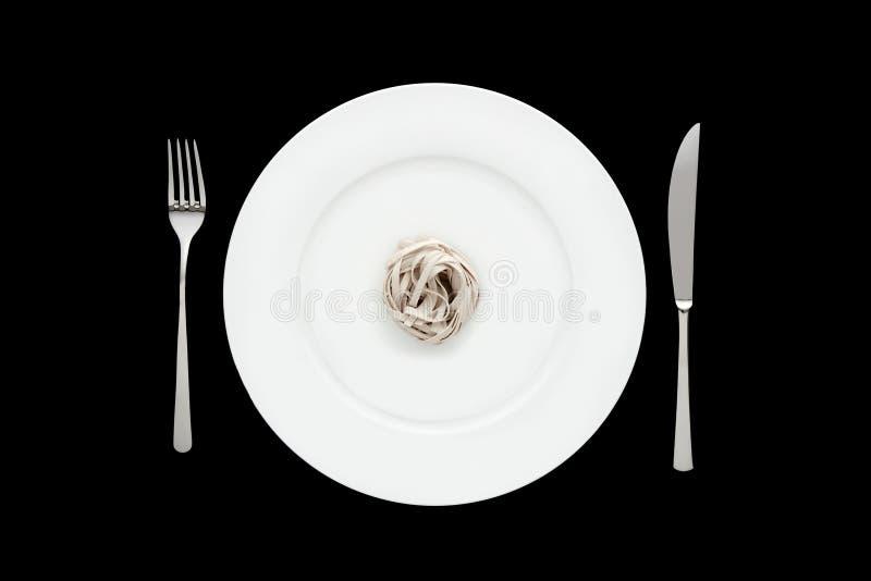 Pequeña porción de pastas de los tallarines en la placa blanca redonda con la bifurcación y el cuchillo en fondo negro aislado fotos de archivo libres de regalías