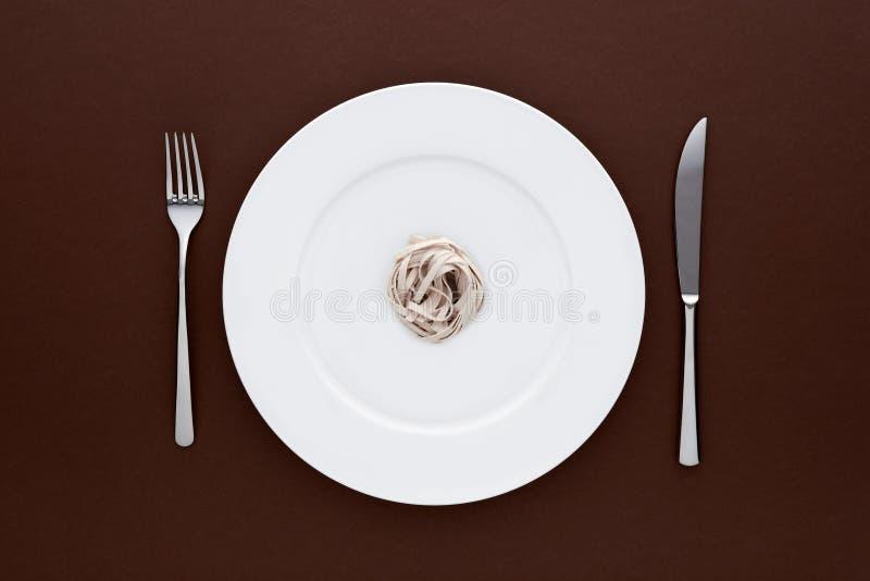 Pequeña porción de pastas de los tallarines en la placa blanca redonda con la bifurcación y el cuchillo en mantel marrón oscuro foto de archivo libre de regalías