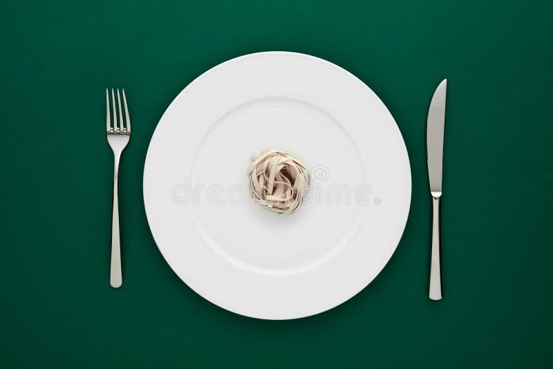 Pequeña porción de pastas de los tallarines en la placa blanca redonda con la bifurcación y el cuchillo en mantel verde fotografía de archivo