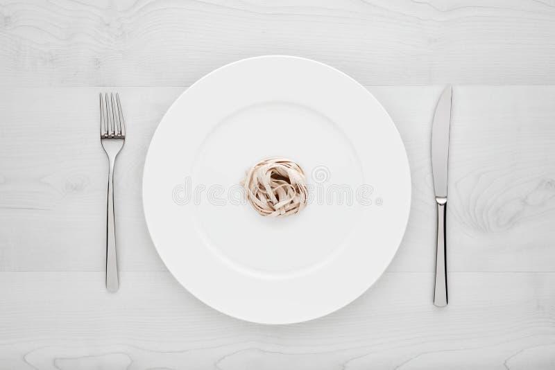 Pequeña porción de pastas de los tallarines en la placa blanca redonda con la bifurcación y el cuchillo en una tabla de madera bl imágenes de archivo libres de regalías