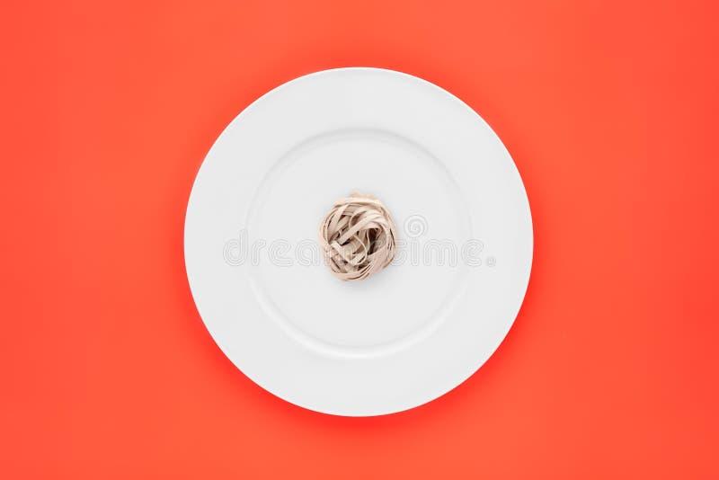 Pequeña porción de pastas de los tallarines en la placa blanca redonda en fondo anaranjado imagenes de archivo