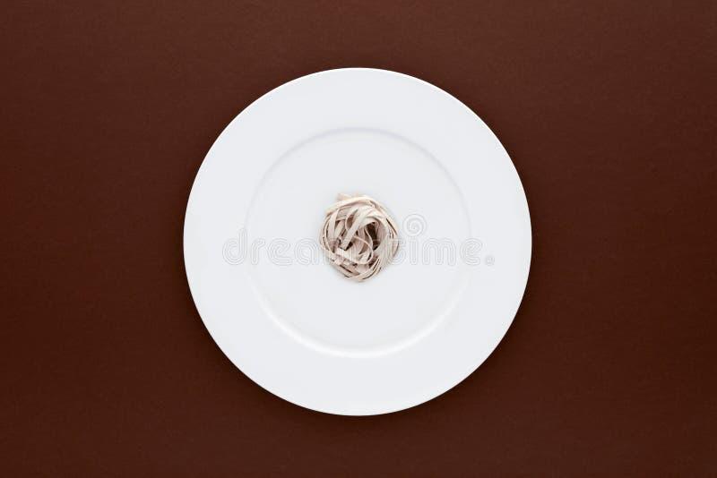 Pequeña porción de pastas de los tallarines en la placa blanca redonda en fondo marrón foto de archivo