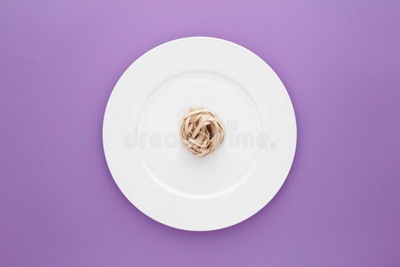 Pequeña porción de pastas de los tallarines en la placa blanca redonda en fondo purpúreo claro foto de archivo