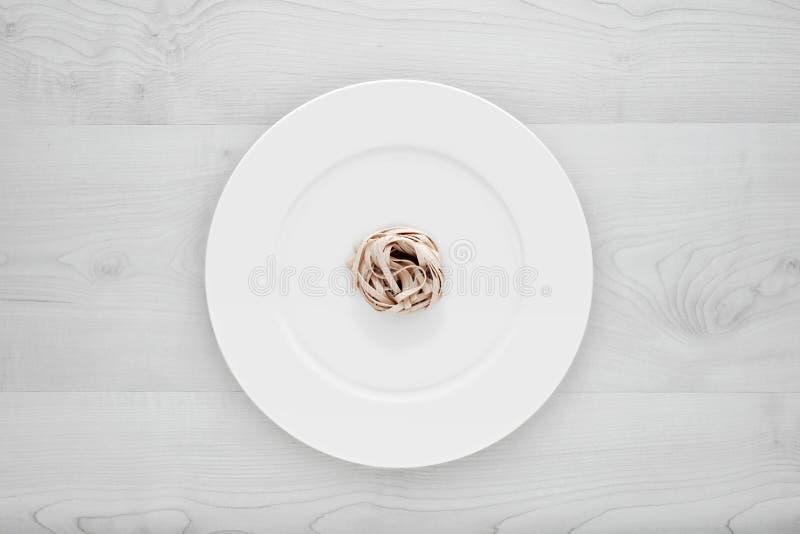 Pequeña porción de pastas de los tallarines en la placa blanca redonda en una tabla de madera blanca Concepto de dieta, sanos y m fotos de archivo libres de regalías