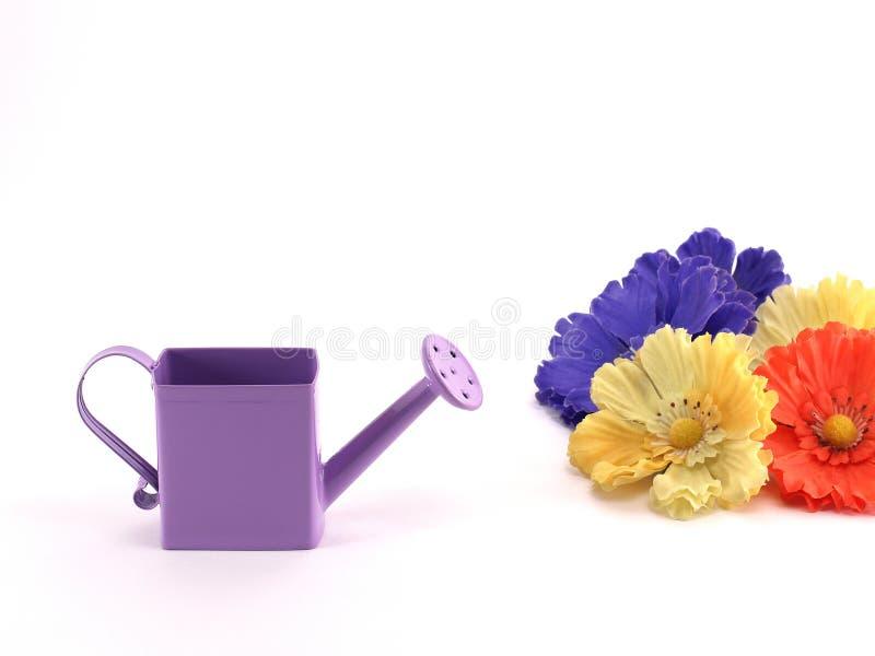 Pequeña regadera y flores coloridas de la tela foto de archivo