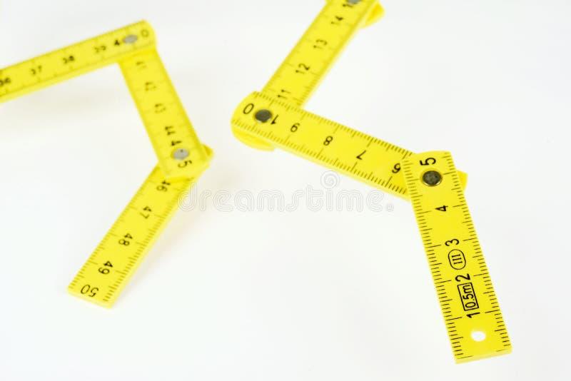 Pequeña regla de plegamiento amarilla en el fondo blanco imágenes de archivo libres de regalías