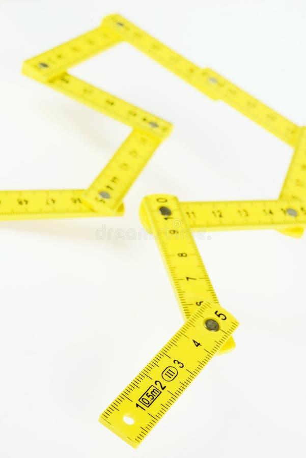 Pequeña regla de plegamiento amarilla en el fondo blanco fotografía de archivo