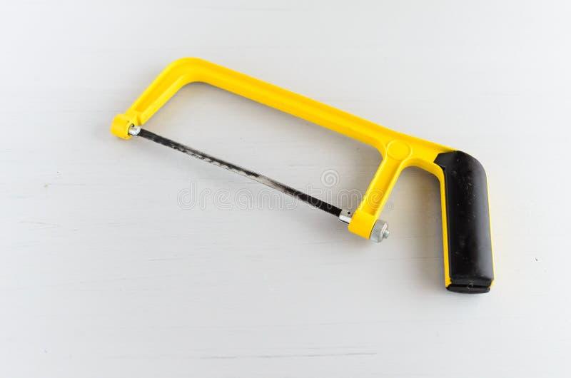 Pequeña sierra de mano del uso en el hogar a la madera o al plástico que asierra foto de archivo libre de regalías