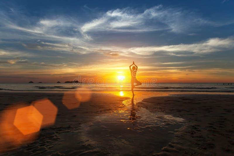 Pequeña silueta de una yoga practicante de la mujer en la playa del mar imágenes de archivo libres de regalías